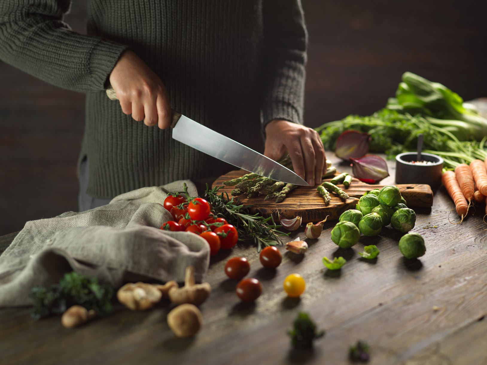Food photography with model cutting fresh vegetables