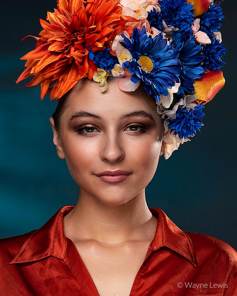 Portrait of girl with floral hat against blue backdrop by Wayne Lewis