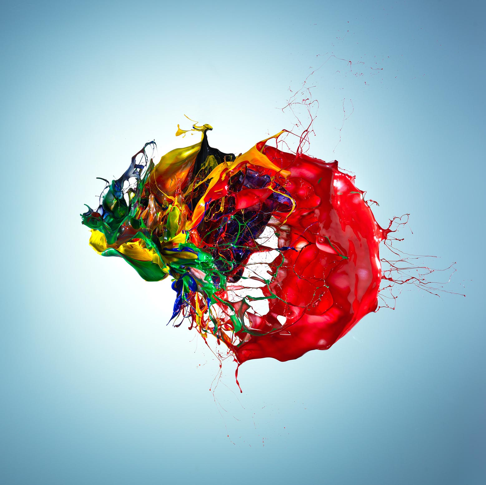 Explosion of colourful paint on a graduated blue background
