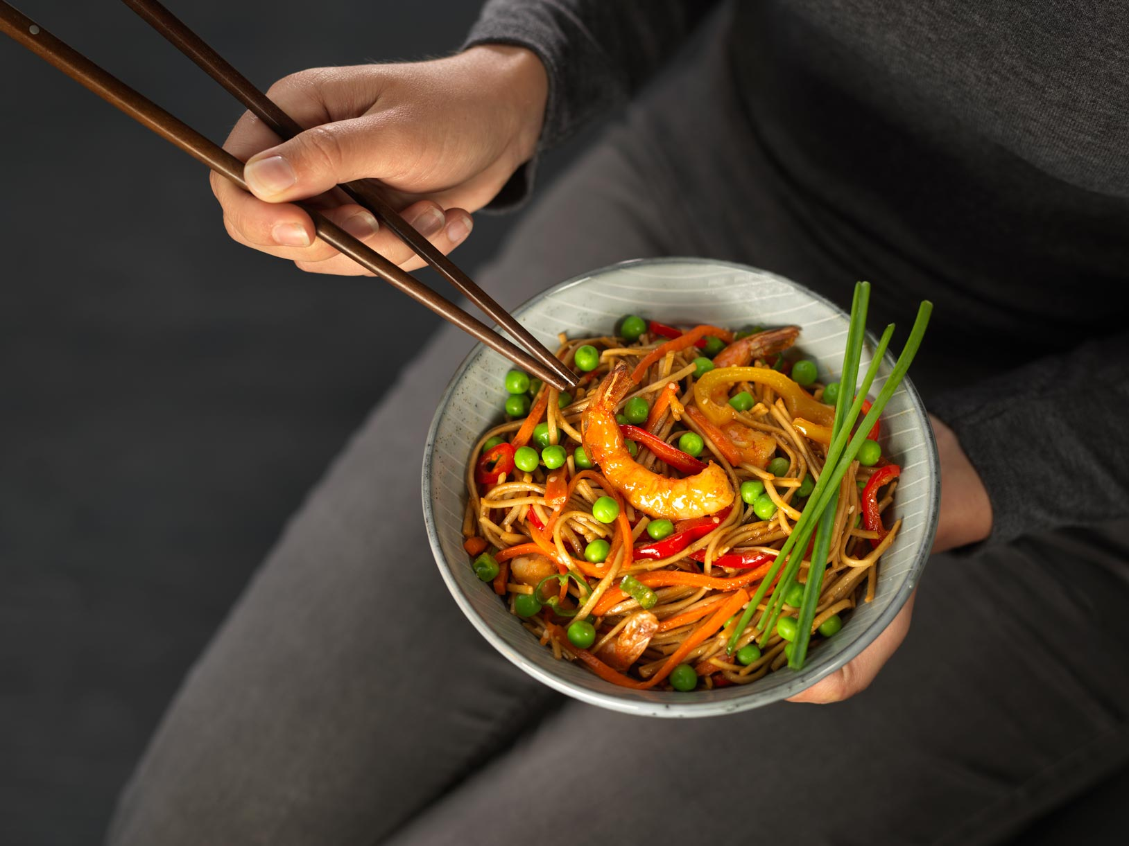 Person holding a bowl of prawn stiry fry
