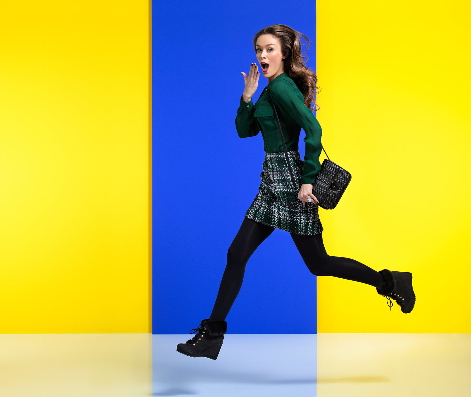 Model running against yellow and blue background