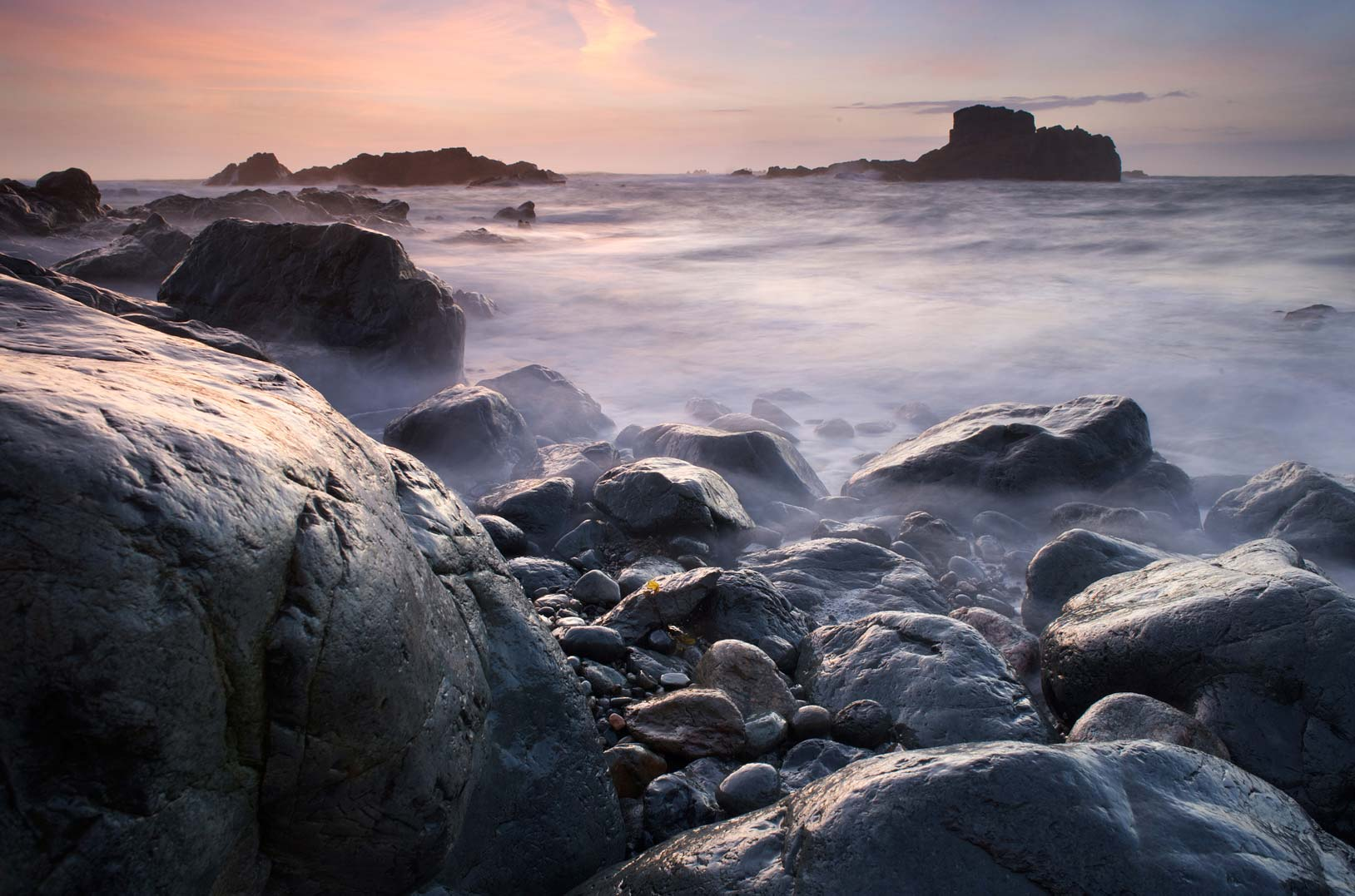 Seascape landscape image with rocks in the foreground